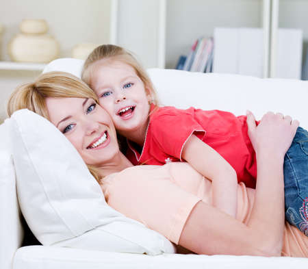 Beautiful happy family of young blond mother and her little pretty daughter - indoors photo