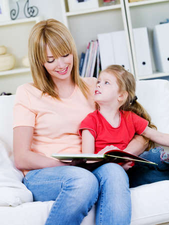 Portrait of young happy  mother studing her little daughter to read - at home photo