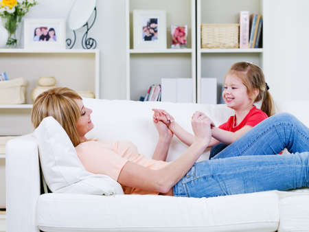 Happy young  mother relaxing on the sofa and playing with her little daughter - indoors photo
