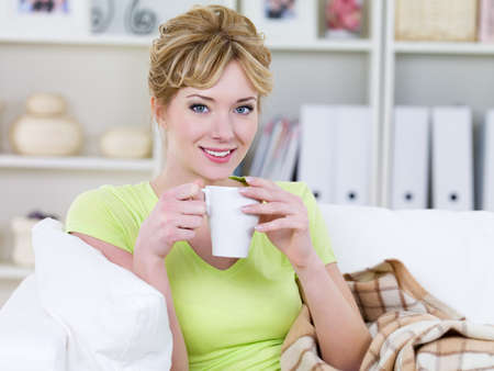 Portrait of smiling beautiful pretty young woman drinking hot coffee at home - indoors photo