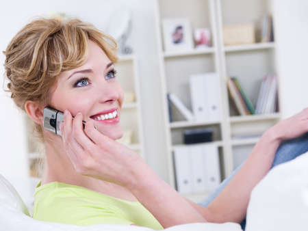 Portrait of smiling beautiful cheerful woman with mobile speaking - indoors photo
