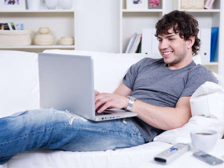 Handsome young relaxing man using laptop and lying on the sofa photo