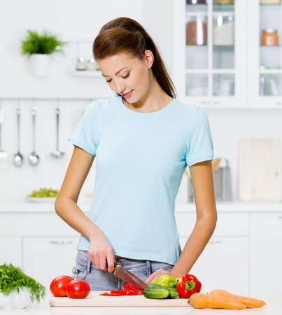 Mooie vrouw koken gezonde voeding in de keuken - binnenshuis