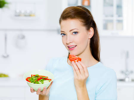 woman eat: smiling woman eat vegetable on the kitchen Stock Photo