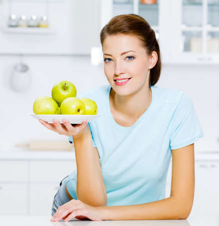 nutrition health:  happy woman with green apples on a plate on kitchen Stock Photo