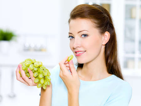 woman eat: beautiful woman eating  grapes is on the kitchen  Stock Photo