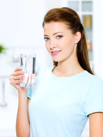 water beautiful: Beautiful young woman holds a glass with water on kitchen