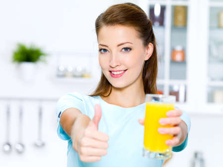 orange juice glass: successful young woman thumbs-up with a glass of fresh orange juice  Stock Photo