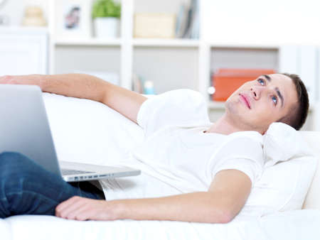 young guy with laptop look outside on the sofa photo