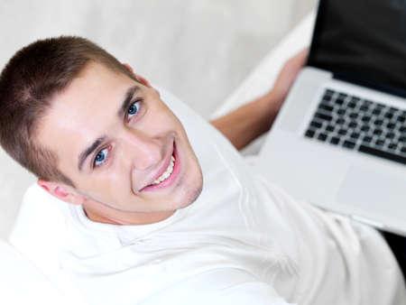 high angle: happy young guy using laptop and lying on the sofa - high angle Stock Photo