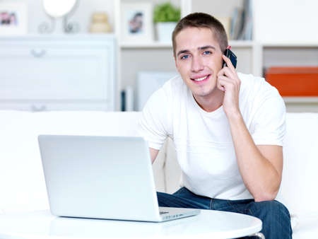happy young man speaks on the phone and works on the laptop at home photo