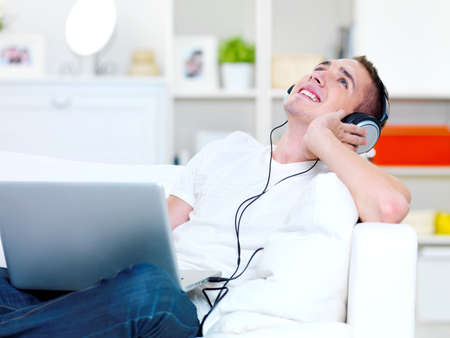 happy guy listening music in headphone from laptop and lying on the sofa photo