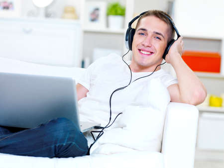 Smiling young guy listening music in headphone from laptop at home photo