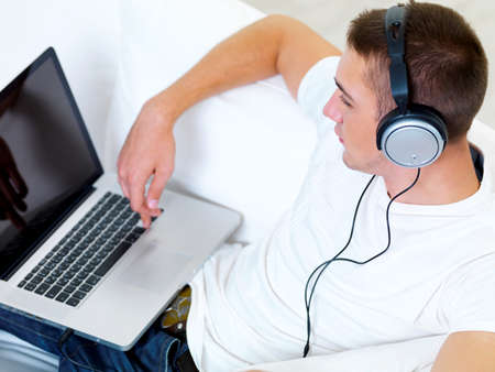 portrait profile young guy listening music in headphone from laptop at home photo