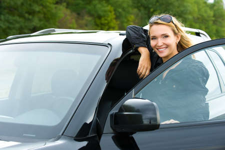 test drive: portrait of attractive young happy woman in the new car  - outdoors Stock Photo