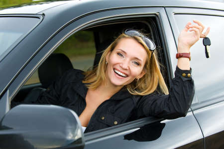 key to success: successful beautiful happy woman in the new car with keys - outdoors