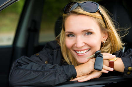 car keys: portrait of beautiful young smiling woman in the new car with keys - outdoors