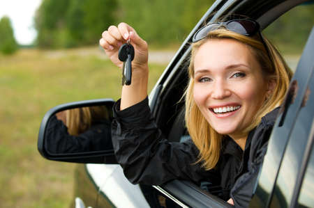 Beautiful young happy woman in  car showing the keys - outdoors photo