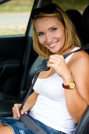 seat belt: Beautiful young happy woman fastens a seat belt in the car - outdoors Stock Photo