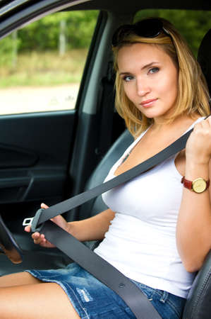 safe driving: Beautiful young woman fastens a seat belt in the car - outdoors Stock Photo