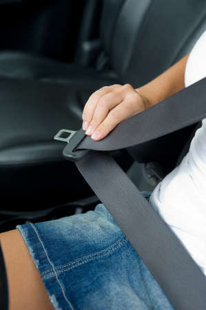 womans hand with seat belt in the car - outdoors photo
