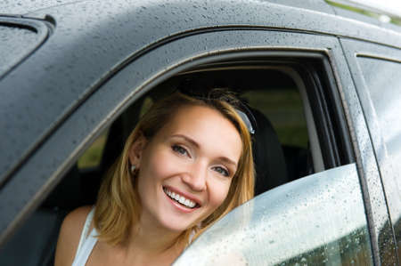 portrait of beautiful young happy woman in the new car  - outdoors photo
