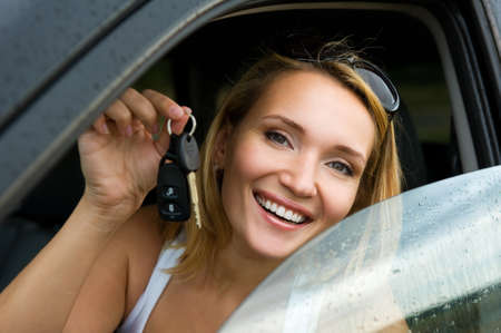 Beautiful young happy woman in the new car with keys - outdoors photo