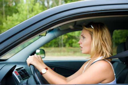 profile face: Profile face of fright woman sitting in the car and holds the wheel - outdoors