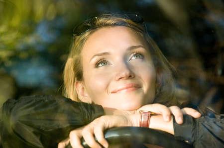dream car: Atractivo sonriente sue�os de la mujer en el nuevo coche y buscar - al aire libre