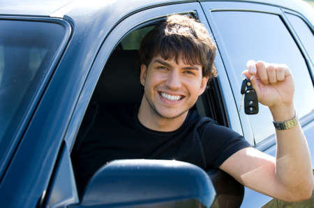 car driver: portrait of successful young happy man showing the keys sitting in new car