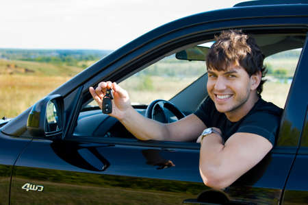 car park: Successful young happy man showing the keys sitting in new car