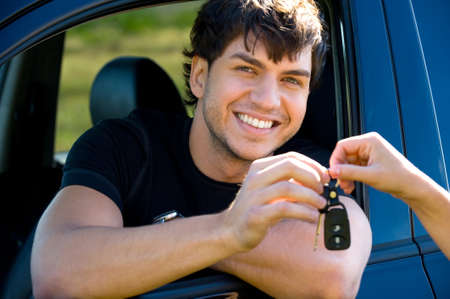 Successful young happy man showing the keys sitting in new car photo