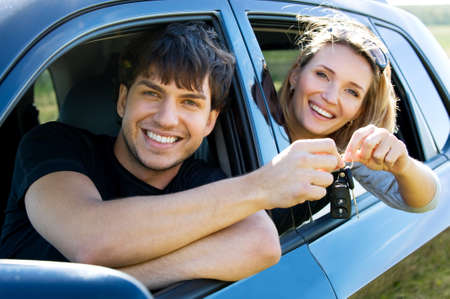 Happy bautiful couple showingh the keys sitting in new car  photo