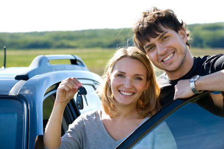 portrait of happy bautiful couple showingh the keys standing near the car  photo