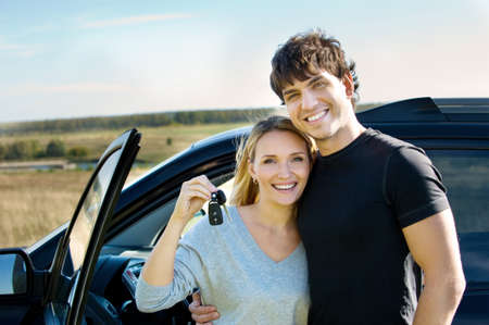 car driver: portrait of happy bautiful couple showingh the keys standing near the car