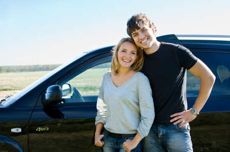 happy bautiful young couple standing near the car photo