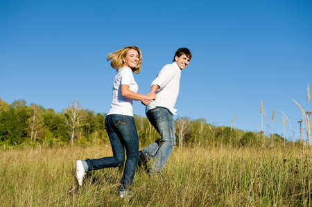 Happy young couple running on summer meadow Stock Photo - 8040914