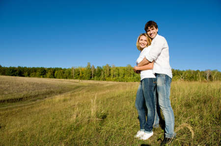 full-length portrait of happy young couple standing on summer meadow Stock Photo - 8040911