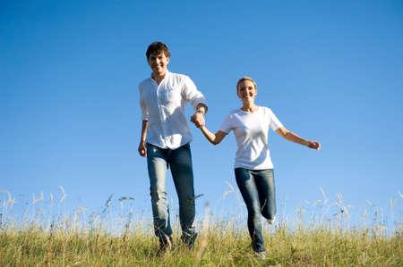 Feliz pareja joven que se ejecutan en la pradera de verano