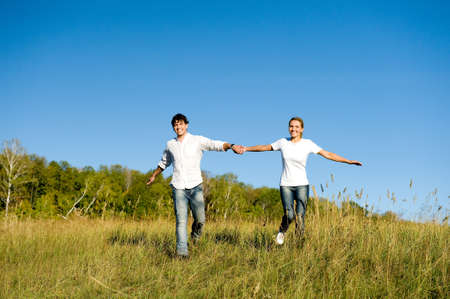 Happy young couple running on summer meadow photo