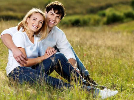 romantic sexy couple: young happy beautiful couple sitting in green meadow