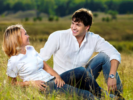 happy beautiful couple sitting in green meadow and looking against each other  photo