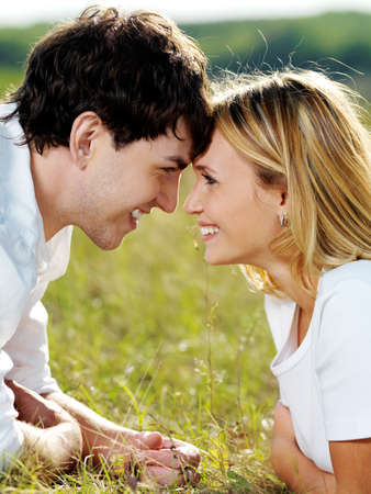 portrait of young happy  flirting couple lying  in green meadow and looking against each other  photo