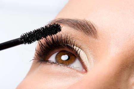 Woman applying mascara on her eyelashes - macro shot photo