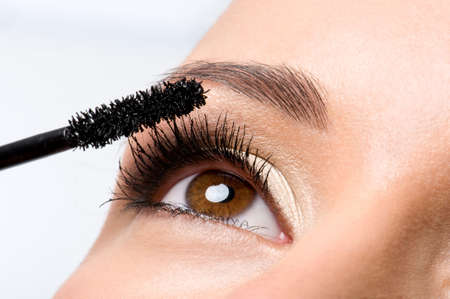 mascara: Woman applying mascara on her eyelashes - macro shot