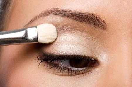 makeup applying: woman applying eyeshadow on eyelid using makeup brush Stock Photo