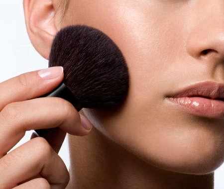 cheek to cheek: woman applying rough on cheek - macro shot Stock Photo