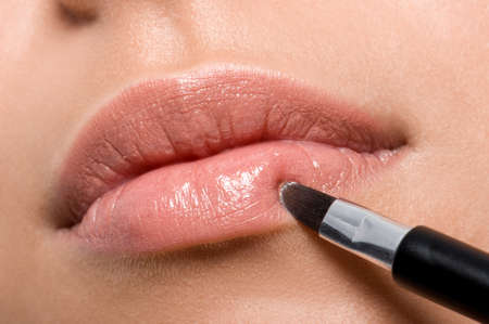 woman applying lipstick on lips with brush - closeup photo