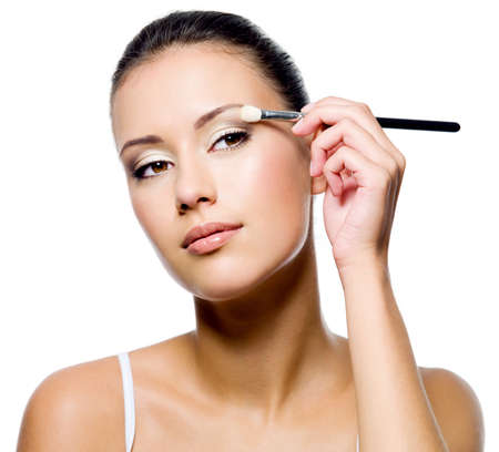 beautiful attractive woman applying eyeshadow with brush on white background Stock Photo - 8040967