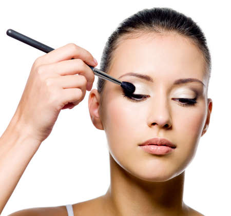 beautiful young woman applying eyeshadow with brush on white background  photo